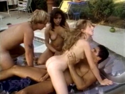 Ginger Lynn and Co. Beautiful, blonde, shapely Ginger Lynn, one of the all-time hottest superstars of x-rated video entertainment, reveals in intimate detail the built-for-sex body and the sexual know-how that has continued to keep her high on everybody's list of wet dream fodder. Her first encounter in this video is with a big-boobed brunette in a swimming pool. Ginger's hands and mouth go into action to turn the other girl on, after which she sits at the side of the pool with her luscious legs spread and lets herself be fingered and kissed and licked. Super-stud Marc Wallace wanders onto the patio, and you can bet that he gets it from both girls at the same time. Is Marc up to the challenge? You bet! As always, his awesome equipment plunges into hot juicy action in a performance that delivers everything you, he and the two horny girls want! The rest of the company is also in the mood for lust. There are two-ways, three-ways, and every which ways, with two girls and a guy, two guys and a girl, and even a four-way with two girls and two guys. One particularly erotic scene involves that incredibly-structured Blondi9 who plays a maid. When tired Tony Montana expresses his desire to get some rest, the Amazonian California girl shows him that he's not as tired as he though he was. The legendary blonde beauty Serena also makes an appearance, letting the parched tongue of a bearded stud satisfy its thirst at her always-soggy fountain, after which the flaxen-haired goddess lets him satisfy her deeper desires of the flesh!