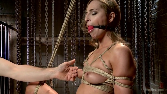 Gorgeous Newcomer Destroyed by Bondage and Squirting Orgasms. Roxy Rox is a beautiful newcomer to the ways of bondage and kink. I make her first scene one to remember by suspending her, gagging her, clipping her nipples and vibing her hot little twat till it spasms out a few intense orgasms while she hangs helplessly in the ropes. When I tie her down on her back, I make sure her long, luscious legs are tied wide open. Mr. Blig Black Dick of Rubber Rubber pounds the fuck out her sweet, tight pussy, and I finish her off with a vibe and a few fingers to the g-spot for some super wet squirting orgasms. At this point her pretty little head is spinning and I get the evil idea to really ramp things up with a Sybian. I tie the vibrating box tight to her twat, bind her to the floor and let 'er rip. As I slowly crank up the intensity of the vibrating machine, I start to add clothespins all over her pretty little tits. Once the thing is running on high, she is coming uncontrollable, unable to escape. No matter what she does she cannot get away from the evil machine. In the end, she is completely spent but very happy. HogTied delivers another beautiful girl fucked silly.