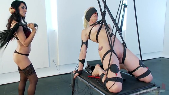 Isis Love Dommes Lorelei Lee Part 2. Lorelei has been dishing out the electricity, and now it's her turn to feel it again. She is totally submissive in this strict and painful bondage position. The EMS pads contract the muscles in her arms and legs so that she cannot hold herself up, the bondage becoming tighter as the electricity gets higher. Isis comes in with the red zappers and blindfolds Lorelei so that she can't see where she'll be shocked next. Combined with the electro-hitachi, this is an electro fuck overload for this blonde!